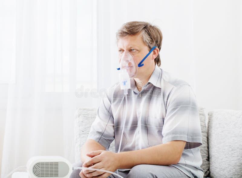 Hombre que inhala a través de máscara del inhalador fotos de archivo