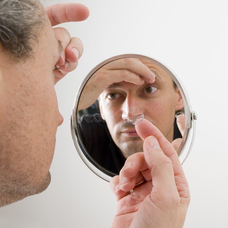 Hombre que inserta una lente de contacto foto de archivo libre de regalías