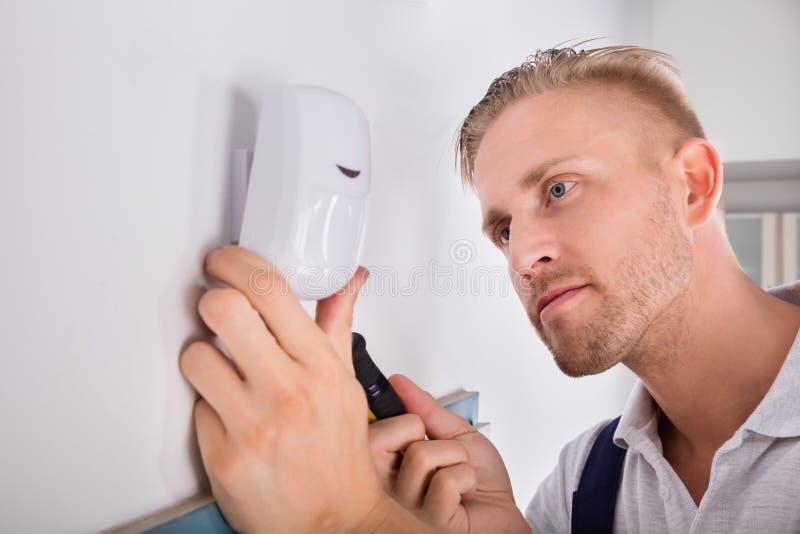 Hombre que instala el detector de movimiento para el sistema de seguridad foto de archivo