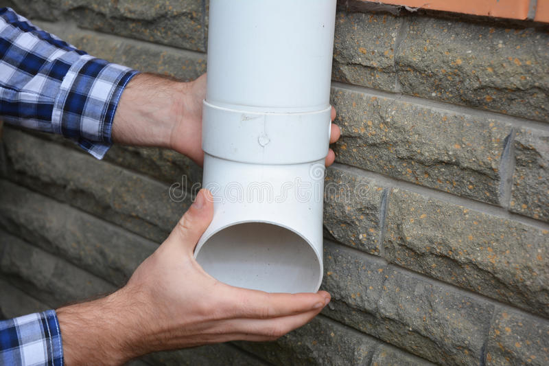 Hombre que instala la tubería plástica del sistema del canal de la lluvia Guttering, canales, Guttering plástico, Guttering y dre fotografía de archivo libre de regalías