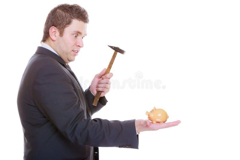 Hombre que intenta romper la hucha con el martillo fotos de archivo