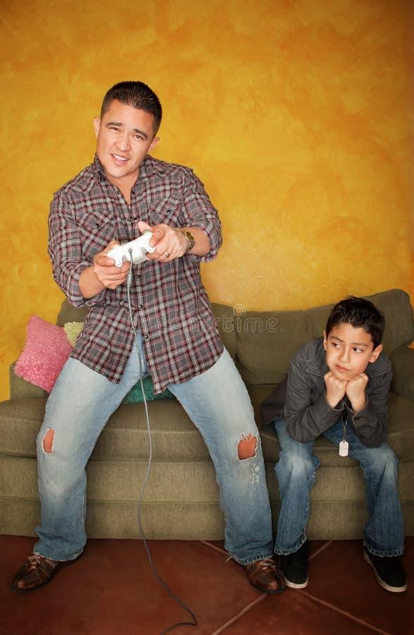 Hombre que juega al juego video con el muchacho joven aburrido foto de archivo libre de regalías