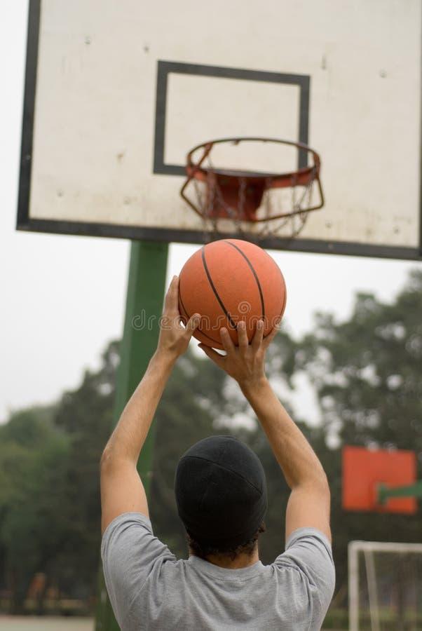 Hombre que juega a baloncesto en la corte en parque - vertical imagenes de archivo