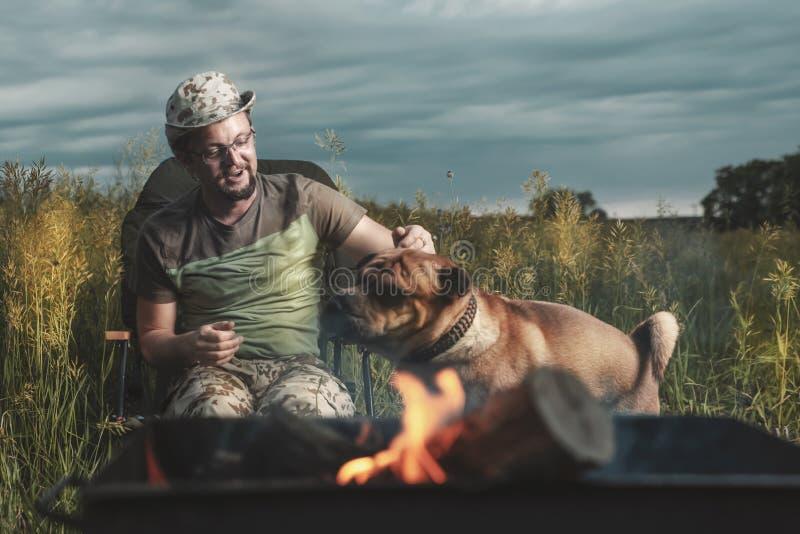 Hombre que juega con un perro de Shar Pei al aire libre teniendo en cuenta el fuego fotos de archivo