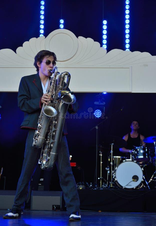 Hombre que juega dos saxofones al mismo tiempo imagenes de archivo