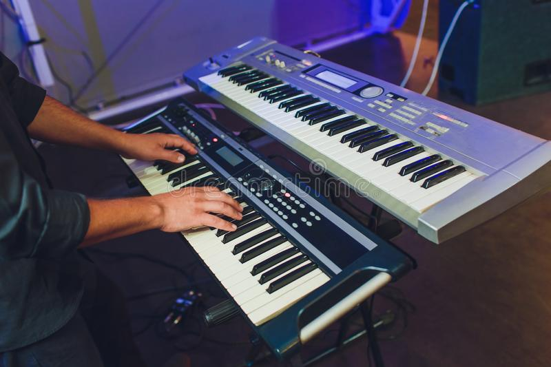 Hombre que juega el sintetizador musical electr?nico del teclado por las manos en las llaves blancas y negras en el estudio de gr foto de archivo