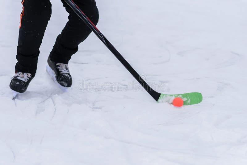 Hombre que juega a hockey con una bola anaranjada fotografía de archivo libre de regalías