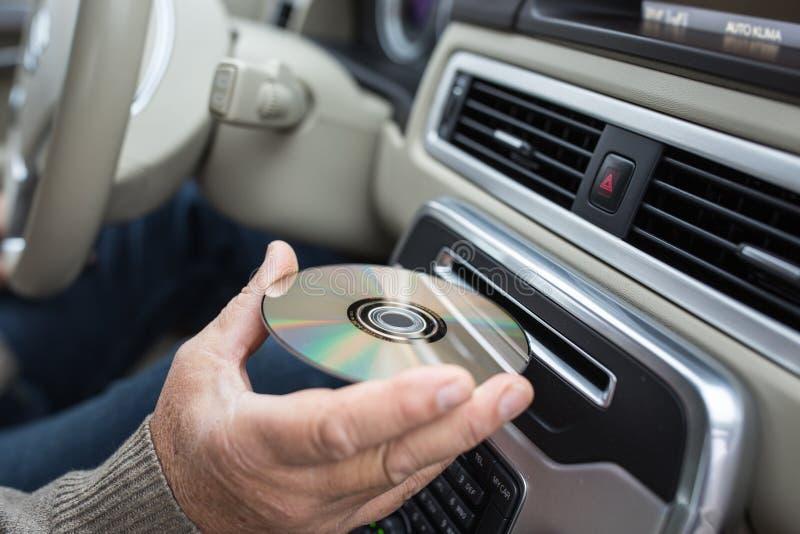 Hombre que juega música en CD DE ALTA FIDELIDAD de inserción automotriz hic en su ranura del lector del CD fotografía de archivo libre de regalías