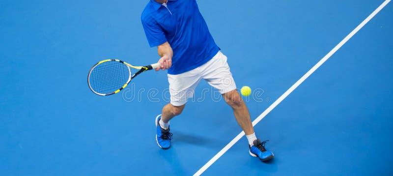 Hombre que juega a tenis en piso azul foto de archivo