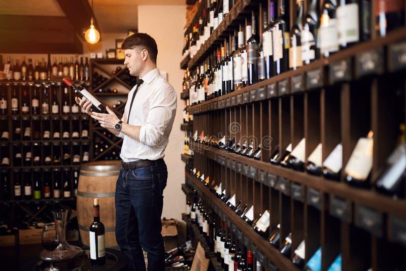 Hombre que lee el contenido de la botella de vino imagen de archivo libre de regalías