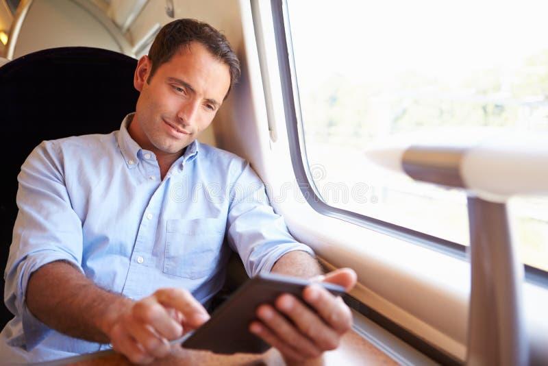 Hombre que lee el libro de E en el tren fotografía de archivo