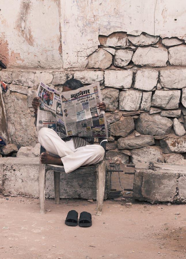 Hombre que lee el periódico indio en la calle fotografía de archivo