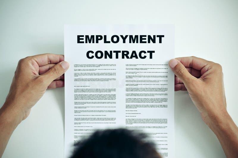 Hombre que lee un contrato de empleo imagenes de archivo