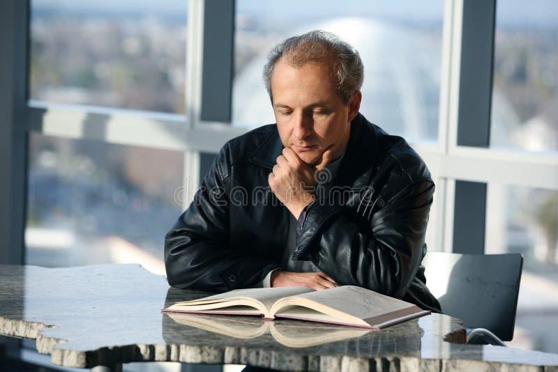Hombre que lee un libro imágenes de archivo libres de regalías