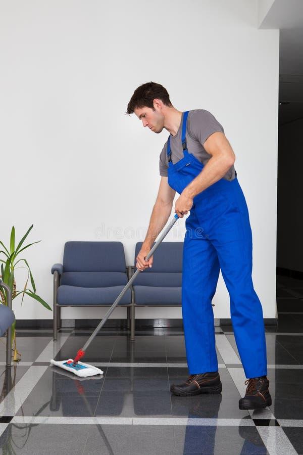 Hombre que limpia el suelo imagen de archivo libre de regalías