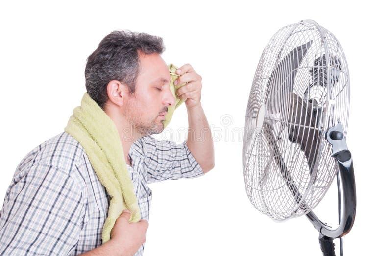 Hombre que limpia la frente sudorosa delante del ventilador fotografía de archivo