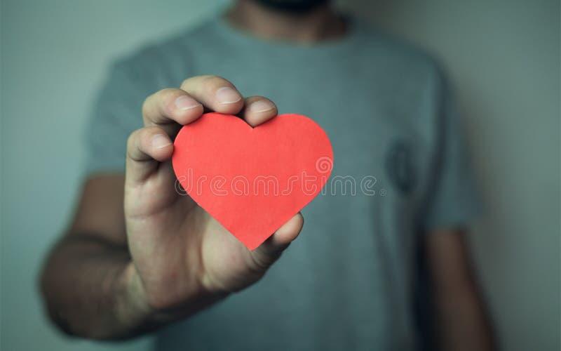 Hombre que lleva a cabo el corazón rojo imagen de archivo libre de regalías