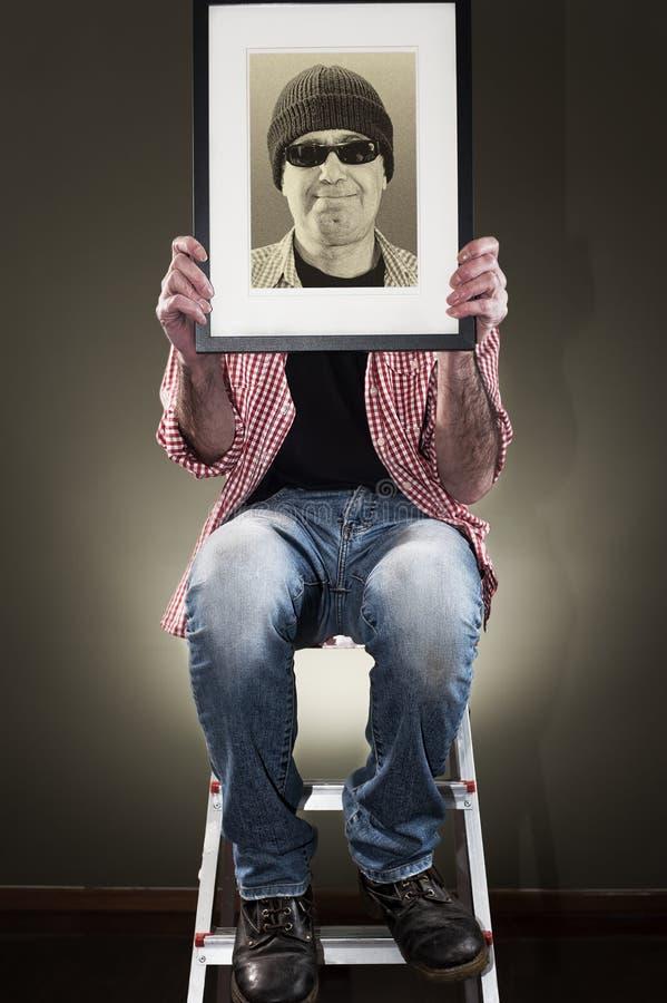 Hombre que lleva a cabo el marco foto de archivo
