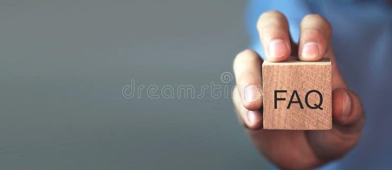 Hombre que lleva a cabo el mensaje del FAQ en el cubo de madera Preguntas con frecuencia hechas imágenes de archivo libres de regalías