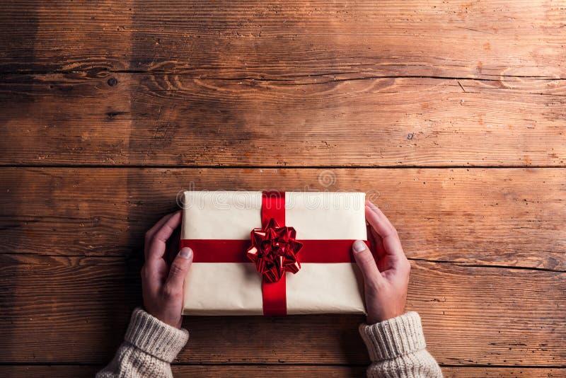 Hombre que lleva a cabo el regalo de Navidad fotos de archivo