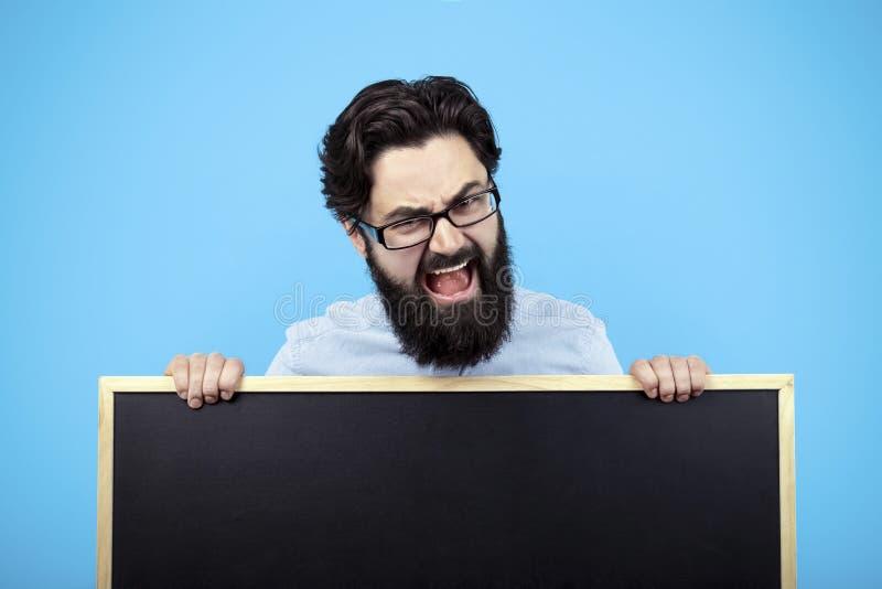 Hombre que lleva a cabo el tablero de tiza imagen de archivo libre de regalías