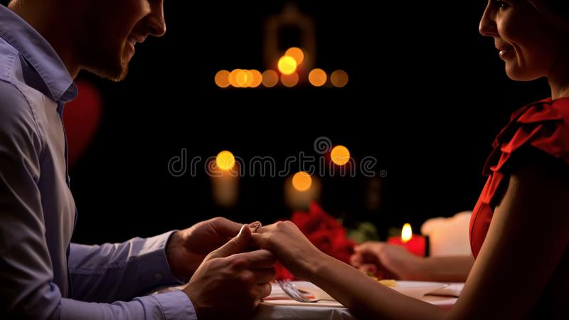 Hombre que lleva a cabo la mano de la mujer, proponiendo matrimonio durante fecha romántica, relaciones fotos de archivo libres de regalías