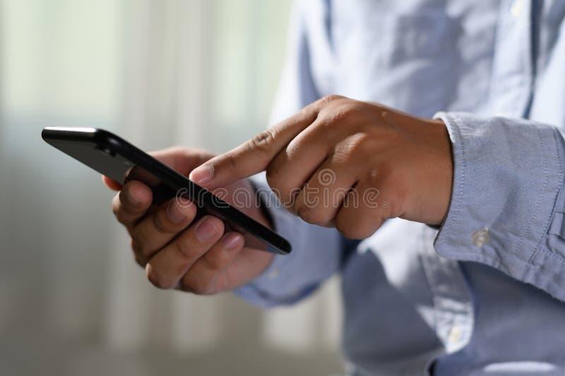 Hombre que lleva a cabo las manos del en y que usa el teléfono digital del teléfono móvil de la tableta con pedregal en blanco de imagen de archivo