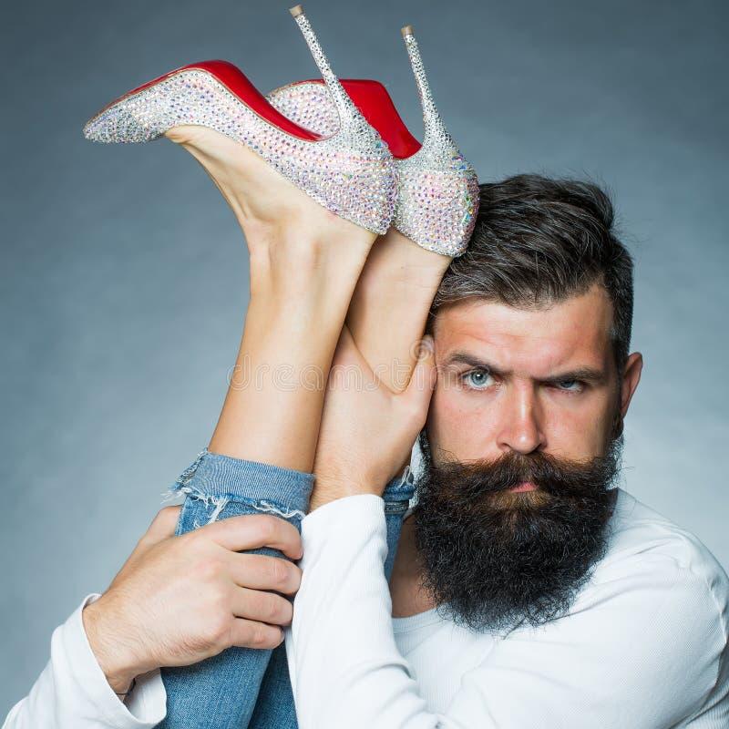 Hombre que lleva a cabo las piernas de la mujer fotografía de archivo