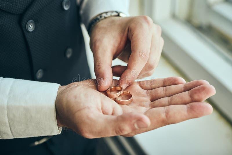 Hombre que lleva a cabo los anillos de bodas, novio que consigue listo por la mañana antes de ceremonia fotografía de archivo libre de regalías