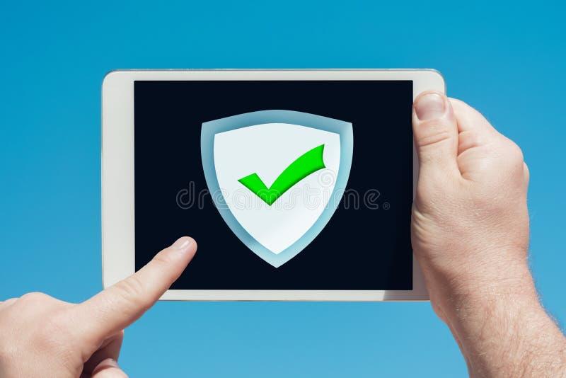 Hombre que lleva a cabo un dispositivo de la tableta que señala en un anti-Spam, icono del cortafuego de la seguridad foto de archivo