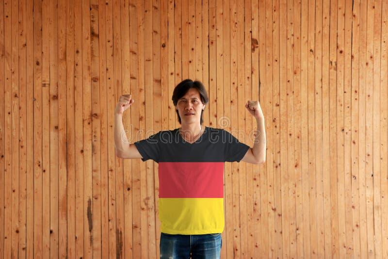 Hombre que lleva el color de la bandera de Alemania de la camisa y que se coloca con el puño aumentado en el fondo de madera de l imagenes de archivo