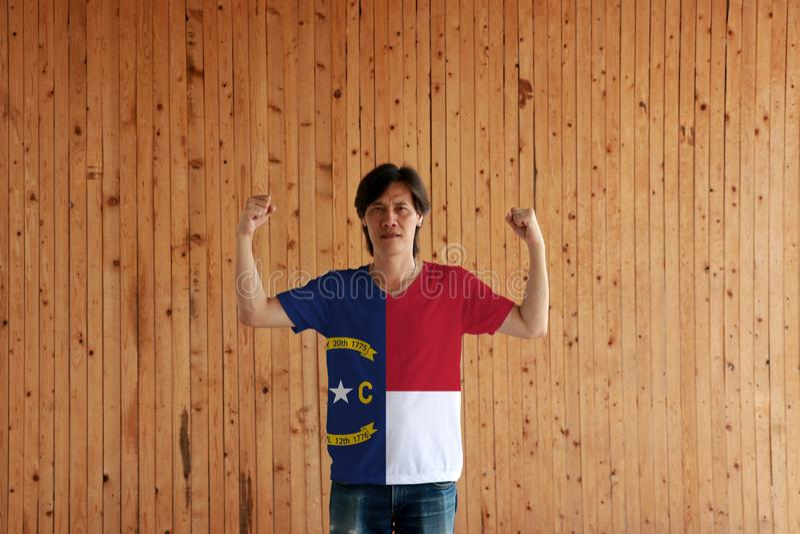 Hombre que lleva el color de la bandera de Carolina del Norte de la camisa y que se coloca con el puño aumentado en el fondo de m imagen de archivo libre de regalías