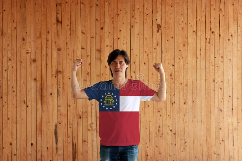 Hombre que lleva el color de la bandera de Georgia de la camisa y que se coloca con el puño aumentado en el fondo de madera de la imagen de archivo