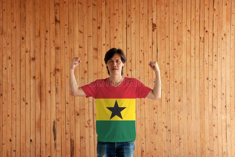 Hombre que lleva el color de la bandera de Ghana de la camisa y que se coloca con el puño aumentado en el fondo de madera de la p foto de archivo libre de regalías