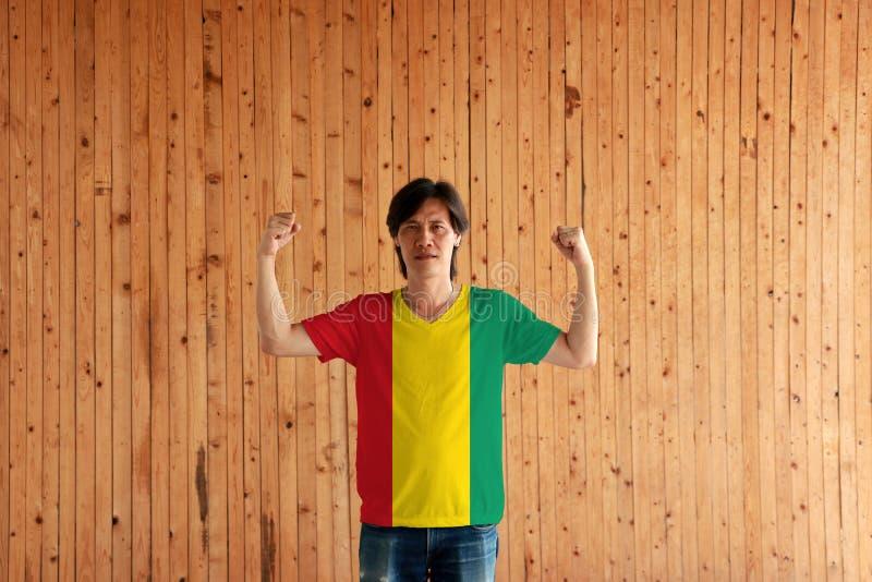 Hombre que lleva el color de la bandera de Guinea de la camisa y que se coloca con el puño aumentado en el fondo de madera de la  imagen de archivo libre de regalías