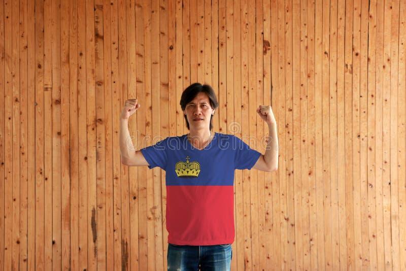 Hombre que lleva el color de la bandera de Liechtenstein de la camisa y que se coloca con el puño aumentado en el fondo de madera fotografía de archivo