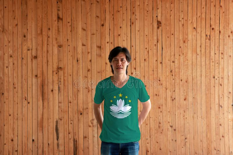 Hombre que lleva el color de la bandera de Macao de la camisa y que se coloca con cruzado detrás de las manos traseras en el fond fotografía de archivo