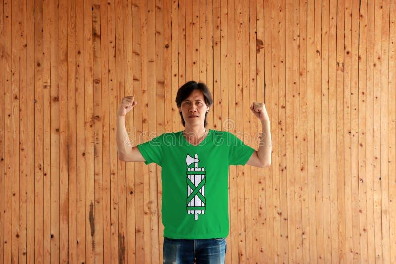 Hombre que lleva el color de la bandera de St Gallen de la camisa y que se coloca con el puño aumentado en el fondo de madera de  fotografía de archivo