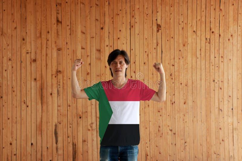 Hombre que lleva el color de la bandera de Sudán de la camisa y que se coloca con el puño aumentado en el fondo de madera de la p imagenes de archivo