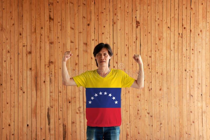 Hombre que lleva el color de la bandera de Venezuela de la camisa y que se coloca con el pu?o aumentado en el fondo de madera de  imagen de archivo libre de regalías