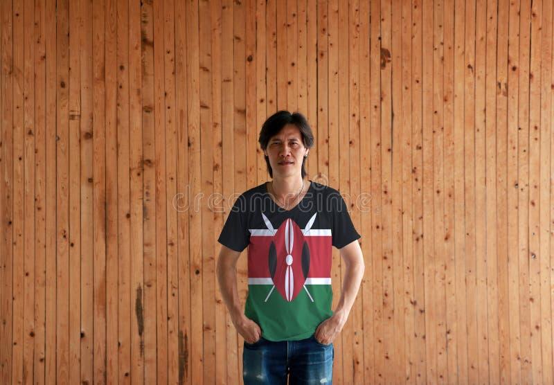 Hombre que lleva la camisa del color de la bandera de Kenia y que se coloca con dos manos en bolsillos de bragas en el fondo de m fotografía de archivo