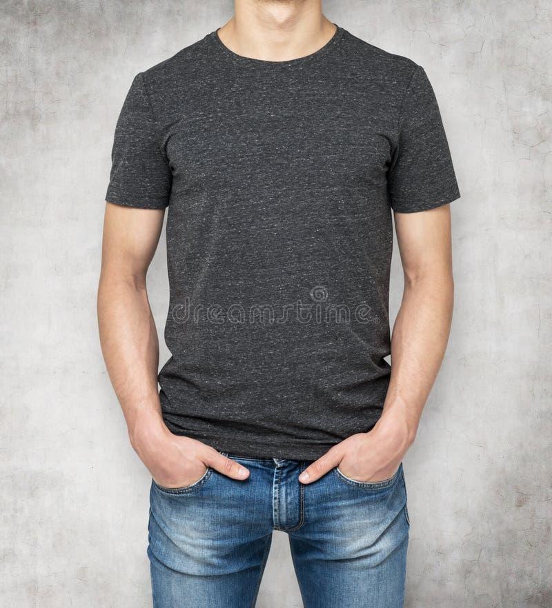 Hombre que lleva la camiseta gris oscuro, fondo concreto imagen de archivo