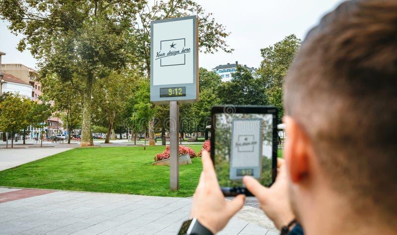 Hombre que lleva la foto con la tableta el cartel publicitario adaptable imagen de archivo