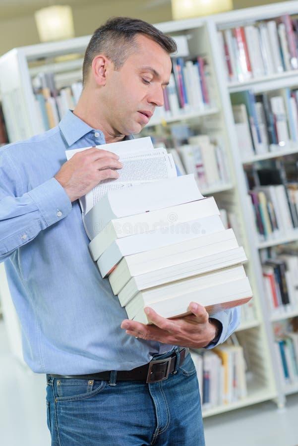 Hombre que lleva los libros precarios de la pila fotografía de archivo libre de regalías