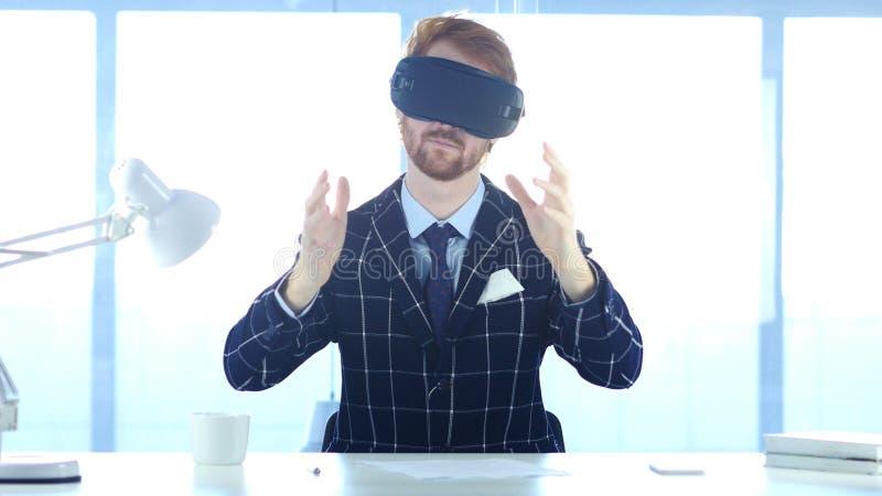 Hombre que lleva los vidrios de la realidad virtual en oficina el usar con las auriculares de las gafas de Smartphone VR ? fotografía de archivo libre de regalías