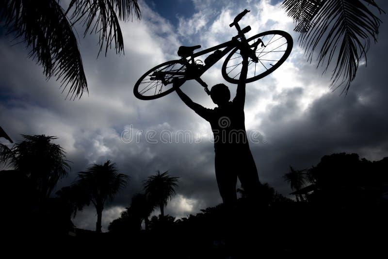 Hombre que lleva su bici imagen de archivo