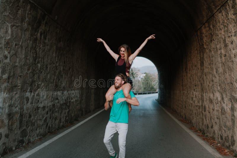 Hombre que lleva a su novia en sus hombros Pares alternativos imágenes de archivo libres de regalías