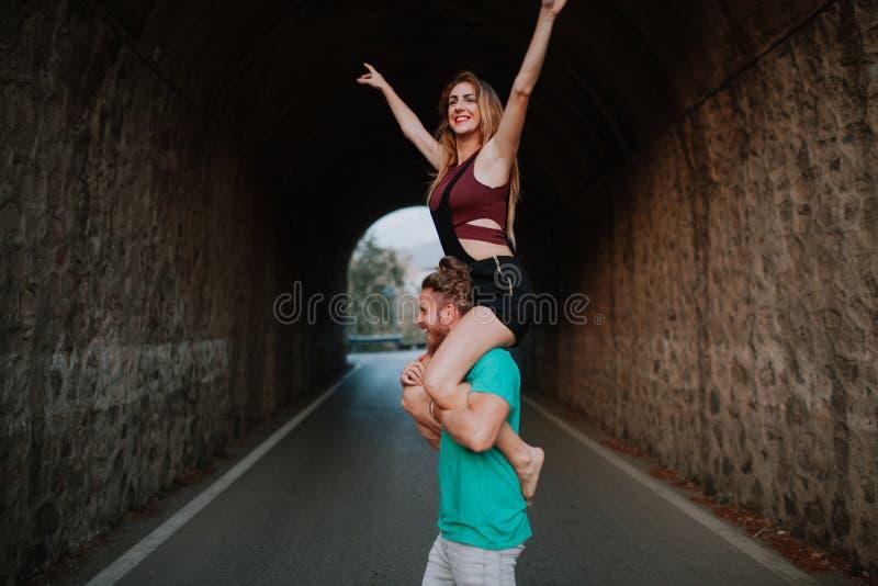 Hombre que lleva a su novia en sus hombros Pares alternativos fotografía de archivo libre de regalías