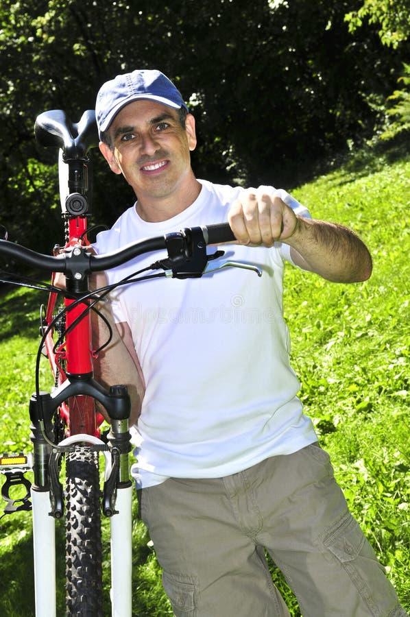 Hombre que lleva una bicicleta fotos de archivo