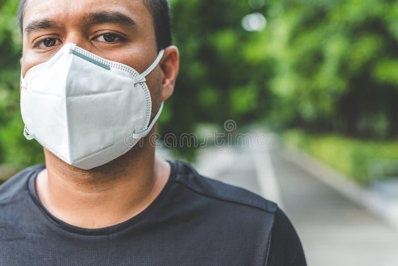 Hombre que lleva una máscara en la calle Protección contra virus imágenes de archivo libres de regalías